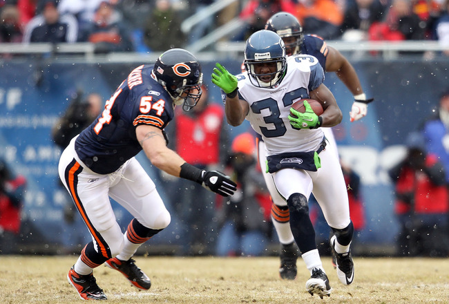 CHICAGO, IL - JANUARY 16:  Leon Washington #33 of the Seattle Seahawks runs the ball against linebacker Brian Urlacher #54 of the Chicago Bears in the first quarter of the 2011 NFC divisional playoff game at Soldier Field on January 16, 2011 in Chicago, I