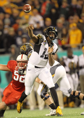 ORLANDO, FL - DECEMBER 28:  Geno Smith #12 of the West Virginia Mountineers passes the ball during the Champs Sports Bowl against the North Carolina State Wolfpack at Florida Citrus Bowl Stadium on December 28, 2010 in Orlando, Florida.  (Photo by Mike Eh