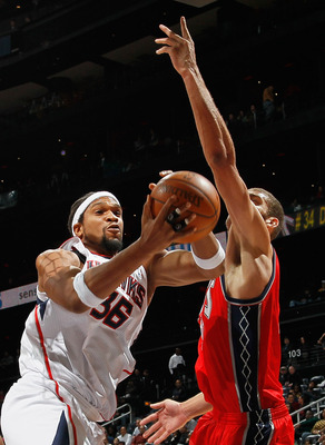 ATLANTA, GA - DECEMBER 07:  Etan Thomas #36 of the Atlanta Hawks grabs a rebound against Brook Lopez #11 of the New Jersey Nets at Philips Arena on December 7, 2010 in Atlanta, Georgia.  NOTE TO USER: User expressly acknowledges and agrees that, by downlo