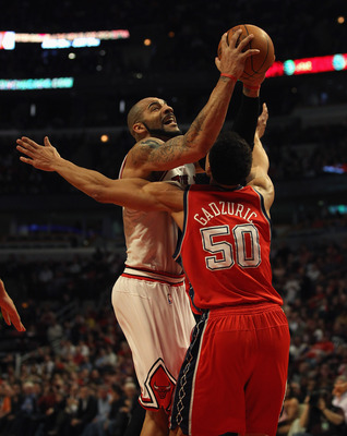 CHICAGO, IL - APRIL 13: Carlos Boozer #5 of the Chicago Bulls drives against Dan Gadzuric #50 of the New Jersey Nets at the United Center on April 13, 2011 in Chicago, Illinois. The Bulls defeated the Nets 97-92. NOTE TO USER: User expressly acknowledges