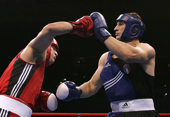 ATHENS - AUGUST 27:  Roberto Cammarelle (blue) of Italy blocks a punch by Alexander Povetkin of Russia during the men's boxing +91 kg semifinal bout on August 27, 2004 during the Athens 2004 Summer Olympic Games at Peristeri Olympic Boxing Hall in Athens,