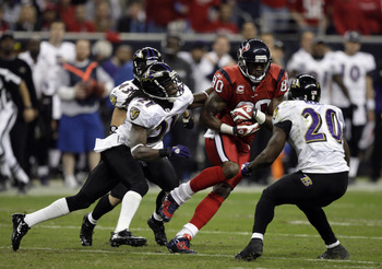 HOUSTON, TX - DECEMBER 13:  Wide receiver Andre Johnson #80 of the Houston Texans is brought down by safety Ed Reed #20 and Ladarius Webb #21 of the Baltimore Ravens at Reliant Stadium on December 13, 2010 in Houston, Texas.  (Photo by Bob Levey/Getty Ima