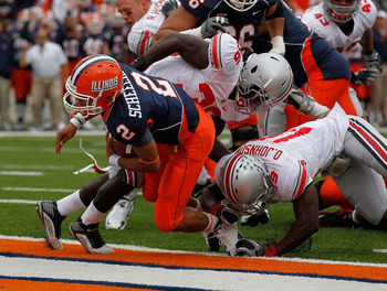 CHAMPAIGN, IL - OCTOBER 02: Nathan Scheelhaase #2 of the Illinois Fighting Illini dives to score a first half touchdown as Orhian Johnson #19 and Brian Rolle #36 of the Ohio State Buckeyes try for the stop at Memorial Stadium on October 2, 2010 in Champai