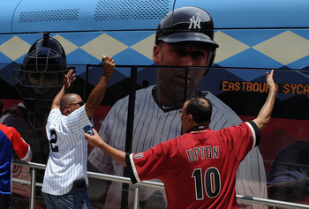 PHOENIX, AZ - JULY 12:  Fans yell as a light rail bus goes in front of fans during the MLB All-Star Game Red Carpet Show and Parade at Chase Field on July 12, 2011 in Phoenix, Arizona. A picture of Derek Jeter #2 of the New York Yankees, who is not attend