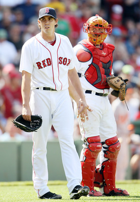 BOSTON, MA - JULY 10:  Kyle Weiland #70 of the Boston Red Sox is consoled by teammate Jason Varitek #33 after Weiland was thrown out of the game after hitting Vladimir Guerrero #27 of the Baltimore Orioles with a pitch on July 10, 2011 at Fenway Park in B
