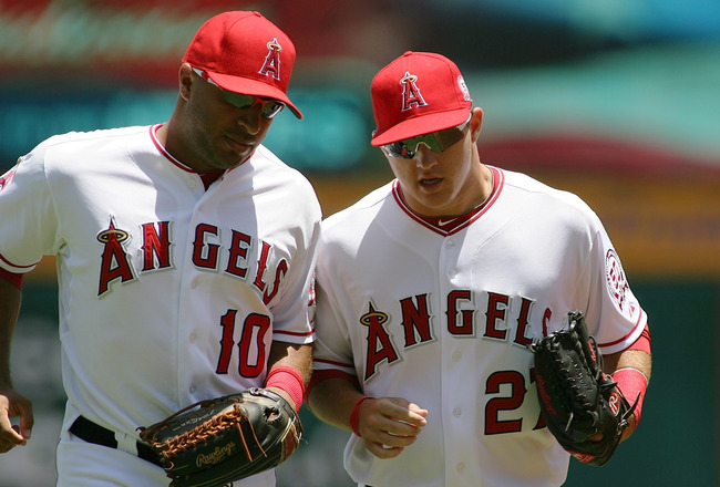 ANAHEIM, CA - JULY 10:  Mike Trout #27 of the Los Angeles Angels of Anaheim talks with teammate Vernon Wells #10 as they jog back to the dugout against the Seattle Mariners at Angel Stadium of Anaheim on July 10, 2011 in Anaheim, California  (Photo by Jef
