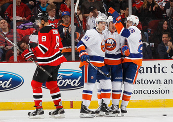 NEWARK, NJ - MARCH 12:  John Tavares #91 of the New York Islanders celebrates his second period goal with teammates Matt Moulson #26 and PA Parenteau #15 as Dainius Zubrus #8 of the New Jersey Devils skates away dejected on March 12, 2011 at the Prudentia