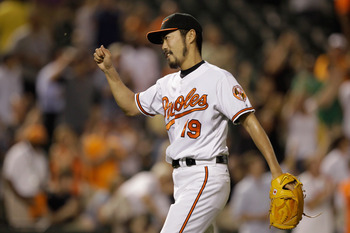 BALTIMORE, MD - JUNE 07: Relief pitcher Koji Uehara #19 of the Baltimore Orioles celebrates after getting the last out during the Orioles 4-0 win over the Oakland Athletics at Oriole Park at Camden Yards on June 7, 2011 in Baltimore, Maryland.  (Photo by
