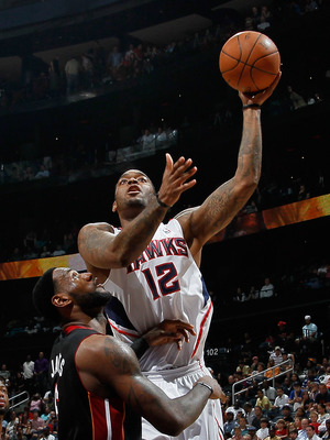 ATLANTA, GA - APRIL 11:  Josh Powell #12 of the Atlanta Hawks shoots over LeBron James #6 of the Miami Heat at Philips Arena on April 11, 2011 in Atlanta, Georgia.  NOTE TO USER: User expressly acknowledges and agrees that, by downloading and/or using thi