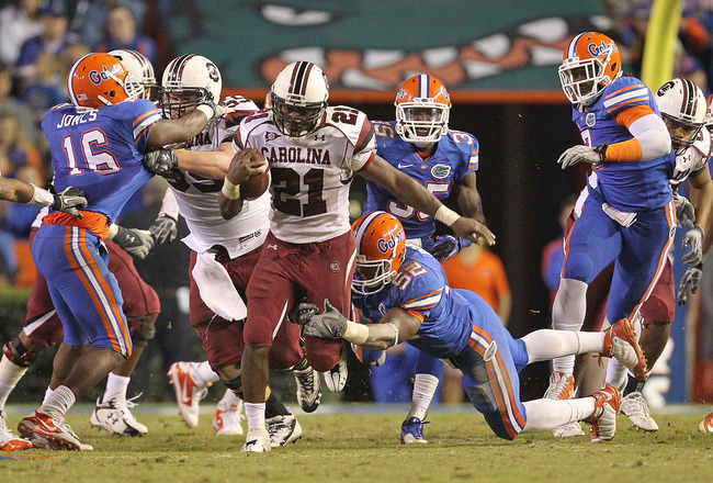 GAINESVILLE, FL - NOVEMBER 13:  Marcus Lattimore #21 of the South Carolina Gamecocks rushes against Jonathan Bostic #52 of the Florida Gators at Ben Hill Griffin Stadium on November 13, 2010 in Gainesville, Florida.  (Photo by Mike Ehrmann/Getty Images)