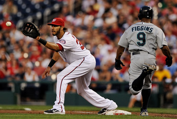 WASHINGTON, DC - JUNE 22: First basemen Michael Morse #38 of the Washington Nationals pulls in a throw to make an out against Chone Figgins #9 of the Seattle Mariners during the sixth inning at Nationals Park on June 22, 2011 in Washington, DC. The Washin