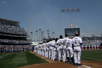 LOS ANGELES - APRIL 13:  The Los Angeles Dodgers stand on the field for the national anthem during opening day ceremonies beofre the game with the Arizona Diamondbacks on April 13, 2010 at Dodger Stadium in Los Angeles, California.  (Photo by Stephen Dunn