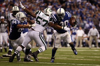 INDIANAPOLIS, IN - JANUARY 08: Dominic Rhodes #30 of the Indianapolis Colts runs the ball against Bart Scott #57 of the New York Jets during their 2011 AFC wild card playoff game at Lucas Oil Stadium on January 8, 2011 in Indianapolis, Indiana.  (Photo by
