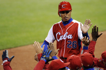 SAN DIEGO - MARCH 16: Leonys Martin #26 of Cuba is congratulated by teammates after scoring a run against Mexico during the 2009 World Baseball Classic Round 2 Pool 1 Game 3 on March 16, 2009 at Petco Park in San Diego, California.  (Photo by Kevork Djans