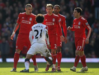 LIVERPOOL, ENGLAND - MARCH 06:  Rafael of Manchester United is confronted by Martin Skrtel (L) and Lucas of Liverpool during the Barclays Premier League match between Liverpool and Manchester United at Anfield on March 6, 2011 in Liverpool, England.  (Pho