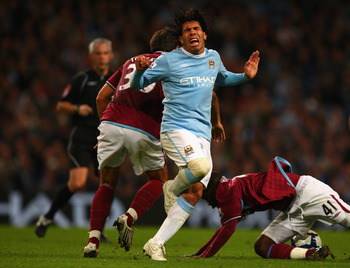 MANCHESTER, ENGLAND - SEPTEMBER 28:  Zavon Hines of West Ham United tangles with Carlos Tevez of Manchester City during the Barclays Premier League match between Manchester City and West Ham United at the City of Manchester Stadium on September 28, 2009 i