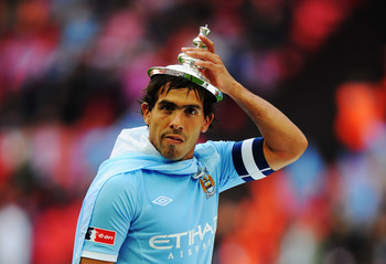 LONDON, ENGLAND - MAY 14:  Carlos Tevez celebrates after he and his Manchester City team mates win the FA Cup sponsored by E.ON Final match between Manchester City and Stoke City at Wembley Stadium on May 14, 2011 in London, England.  (Photo by Mike Hewit