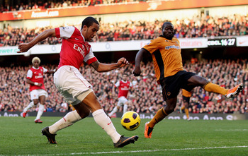LONDON, ENGLAND - FEBRUARY 12:  Theo Walcott of Arsenal (L) attempts to cross the ball past George Elokobi of Wolves during the Barclays Premier League match between Arsenal and Wolverhampton Wanderers on February 12, 2011 in London, England.  (Photo by S