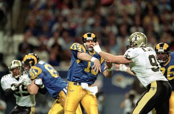 28 Nov 1999: Kurt Warner #13 of the St. Louis Rams passes the ball as his face mask is pulled by Brady Smith #91 of the New Orleans Saints  at the Trans World Dome in St. Louis, Missouri. The Rams defeated the Saints 43-12. Mandatory Credit: Elsa Hasch  /