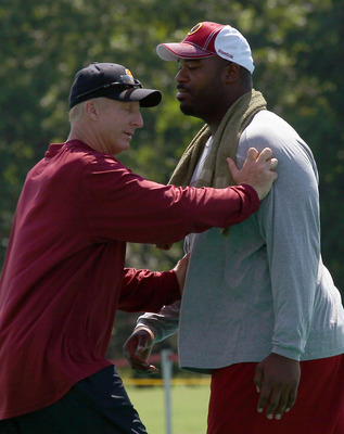 ASHBURN, VA - JULY 30:  Defensive lineman Albert Haynesworth #92 of the Washington Redskins works out with defensive coordinator Jim Haslett (L) following practice on the second day of training camp July 30, 2010 in Ashburn, Virginia. Haynesworth failed a