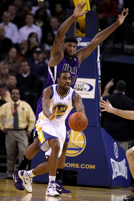OAKLAND, CA - JANUARY 21:  DeMarcus Cousins #15 of the Sacramento Kings defends Reggie Williams #55 of the Golden State Warriors at Oracle Arena on January 21, 2011 in Oakland, California. NOTE TO USER: User expressly acknowledges and agrees that, by down