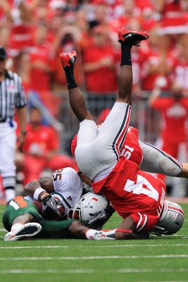COLUMBUS, OH - SEPTEMBER 11:  Leonard Hankerson #85 of the Miami Hurricanes is crushed by C.J. Barnett #4 of the Ohio State Buckeyes after a reception at Ohio Stadium on September 11, 2010 in Columbus, Ohio.  (Photo by Jamie Sabau/Getty Images)