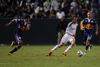 CARSON, CA - SEPTEMBER 24:  David Beckham #23 of the Los Angeles Galaxy paces the ball on the counterattack as Mehdi Ballouchy #10 of New York Red Bulls gives pursuit during the MLS match at The Home Depot Center on September 24, 2010 in Carson, Californi