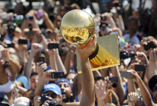 DALLAS, TX - JUNE 16: Dallas Mavericks owner Mark Cuban hoists the Larry O'Brien Trophy up for fans during the Dallas Mavericks Victory Parade on June 16, 2011 in Dallas, Texas. (Photo by Brandon Wade/Getty Images)