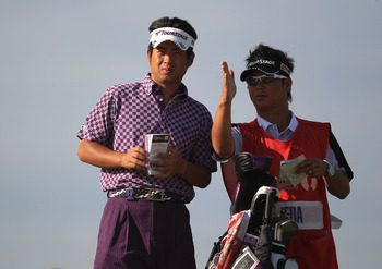SANDWICH, ENGLAND - JULY 15:  Yuta Ikeda of Japan talks with his caddy Hisashi Fukuda during the second round of The 140th Open Championship at Royal St George's on July 15, 2011 in Sandwich, England.  (Photo by Streeter Lecka/Getty Images)