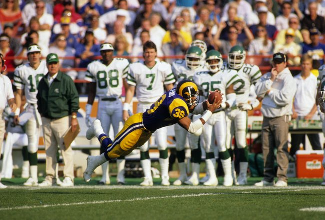 ANAHEIM, CA - DECEMBER 17:  Running back Robert Delpino #39 of the Los Angeles Rams makes a spectacular diving catch in front of an unimpressed New York Jets bench during the game at Anaheim Stadium on December 17, 1989 in Anaheim, California. The Rams wo
