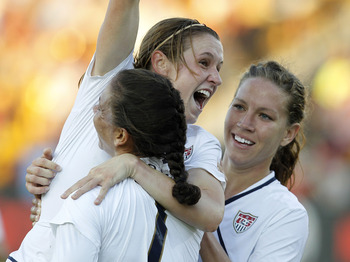 KENNESAW, GA - OCTOBER 02:  Midfielder Heather O'Reilly #9 of the U.S. Women's National Soccer Team (C) is congratulated by teammates Shannon Boxx #7 and Lauren Cheney #12 after her go ahead and game winning goal in the first half during the international