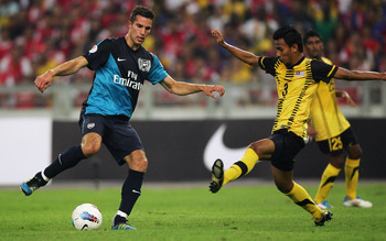 KUALA LUMPUR, MALAYSIA - JULY 13: Robin Van Persie of Arsenal competes with Mohd Farisham Ismail of Malaysia during the pre-season Asian Tour friendly match between Malaysia and Arsenal at Bukit Jalil National Stadium on July 13, 2011 in Kuala Lumpur, Mal
