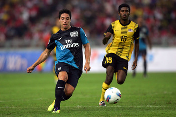KUALA LUMPUR, MALAYSIA - JULY 13: Samir Nasri of Arsenal is pursued by K. Gurasamy of Malaysia during the pre-season Asian Tour friendly match between Malaysia and Arsenal at Bukit Jalil National Stadium on July 13, 2011 in Kuala Lumpur, Malaysia.  (Photo