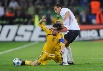 DNEPROPETROVSK, UKRAINE - OCTOBER 10: Rio Ferdinand of England tackles Artem Milevskyi of the Ukraine during the FIFA 2010 World Cup Group 6 Qualifying match between Ukraine and England at the Dnipro Arena on October 10, 2009 in Dnepropetrovsk, Ukraine.