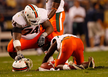 PITTSBURGH - SEPTEMBER 23:  Jacory Harris #12 of the Miami Hurricanes lays on the ground as teammate Orlando Franklin #74 looks on after being sacked by the Pittsburgh Panthers on September 23, 2010 at Heinz Field in Pittsburgh, Pennsylvania.  (Photo by J