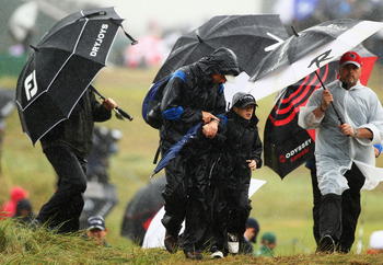 SANDWICH, ENGLAND - JULY 16:  Spectators struggle with the weather conditions during the third round of The 140th Open Championship at Royal St George's on July 16, 2011 in Sandwich, England.  (Photo by Scott Halleran/Getty Images)