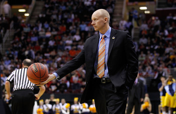 CLEVELAND, OH - MARCH 18: Head coach Chris Mack of the Xavier Musketeers tosses the ball to a referee during the game against the Marquette Golden Eagles during the second round of the 2011 NCAA men's basketball tournament at Quicken Loans Arena on March