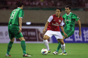 HANGZHOU, CHINA - JULY 16:  Samir Nasri(C) of Arsenal battles for the ball during the pre-season friendly match between Hangzhou Greentown and Arsenal at Yiwu Meihu Stadium on July 16, 2011 in Hangzhou, China.  (Photo by Lintao Zhang/Getty Images)