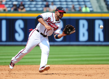 ATLANTA - JULY 7: Alex Gonzalez #2 of the Atlanta Braves fields a grounder against the Colorado Rockies at Turner Field on July 7, 2011 in Atlanta, Georgia. (Photo by Scott Cunningham/Getty Images)