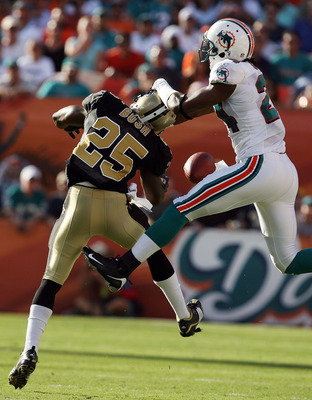 MIAMI - OCTOBER 25:  Running back Reggie Bush #25 of the New Orleans Saints has the ball knocked away by cornerback Sean Smith #24 of the Miami Dolphins at Land Shark Stadium on October 25, 2009 in Miami, Florida.  (Photo by Doug Benc/Getty Images)