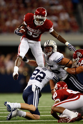 ARLINGTON, TX - SEPTEMBER 05:  Wide receiver Ryan Broyles #85 of the Oklahoma Sooners jumps over Andrew Rich #22 and Brandon Bradley #5 of the Brigham Young Cougars at Cowboys Stadium on September 5, 2009 in Arlington, Texas.  (Photo by Ronald Martinez/Ge