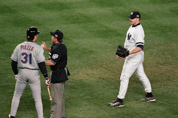 NEW YORK - OCTOBER 22:  Pitcher Roger Clemens #22 of the New York Yankees watches as Mike Piazza #31 of the New York Mets argues with the home plate umpire during game 2 of the World Series at Yankee Stadium in New York, New York on October 22, 2000.  The