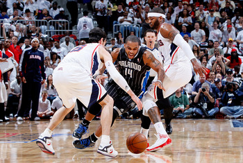 ATLANTA, GA - APRIL 24:  Jameer Nelson #14 of the Orlando Magic loses the ball as he dribbles between Kirk Hinrich #6 and Josh Smith #5 of the Atlanta Hawks during Game Four of the Eastern Conference Quarterfinals in the 2011 NBA Playoffs at Philips Arena