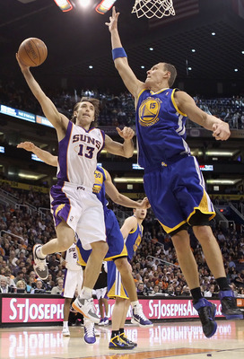 PHOENIX, AZ - FEBRUARY 10:  Steve Nash #13 of the Phoenix Suns lays up a shot past Andris Biedrins #15 of the Golden State Warriors during the NBA game at US Airways Center on February 10, 2011 in Phoenix, Arizona.  NOTE TO USER: User expressly acknowledg