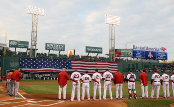 BOSTON, MA - MAY 02:  The Boston Red Sox and the Los Angeles Angels watch the flag cover the Green Monster as the national anthem is played on May 2, 2011 at Fenway Park in Boston, Massachusetts.  Both teams lined up on the baseline to observe a moment of