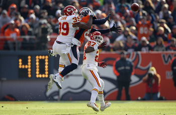 DENVER - NOVEMBER 14:  Wide receiver Brandon Lloyd #84 of the Denver Broncos makes a 37 yard pass reception while under pressure from cornerback Brandon Carr #39 and safety Donald Washington #27 of the Kansas City Chiefs in the first quarter at INVESCO Fi