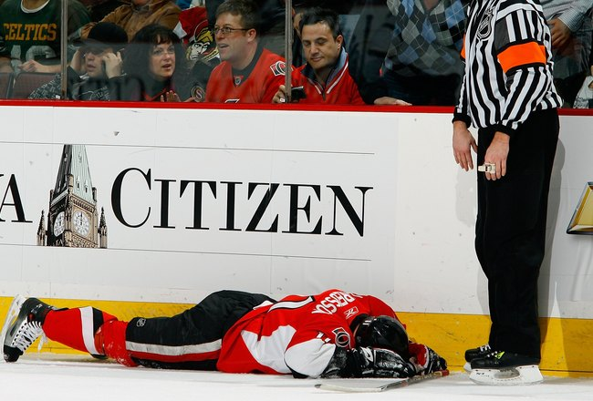 OTTAWA - DECEMBER 20:  An angry fan screams at referee Eric Furlatt through the glass while Daniel Alfredsson #11 of the Ottawa Senators lies injured on the ice after a hit from behind in a game against the Dallas Stars on December 20, 2008 at the Scotiab