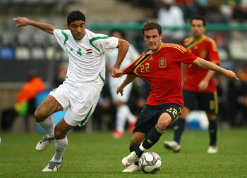 BLOEMFONTEIN, SOUTH AFRICA - JUNE 17:  Juan Manuel Mata of Spain is pulled back by Fareed Majeed of Iraq during the FIFA Confederations Cup match between Spain and Iraq at the Free State Stadium on June 17, 2009 in Bloemfontein, South Africa.  (Photo by A