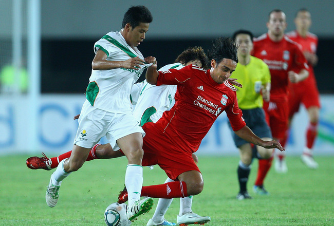 GUANGZHOU, CHINA - JULY 13: Alberto Aquilani (C) of Liverpool challenges Huang Long (L) of Guangdong Sunray Cave during the pre-season friendly match between Guangdong Sunray Cave and Liverpool at Guangdong Provincial People's Stadium on July 13, 2011 in