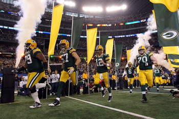 ARLINGTON, TX - FEBRUARY 06:  Ryan Pickett #79, Matt Wilhelm #57, Aaron Rodgers #12 and T.J. Lang #70 of the Green Bay Packers runs out of the tunnel to take on the Pittsburgh Steelers during Super Bowl XLV at Cowboys Stadium on February 6, 2011 in Arling